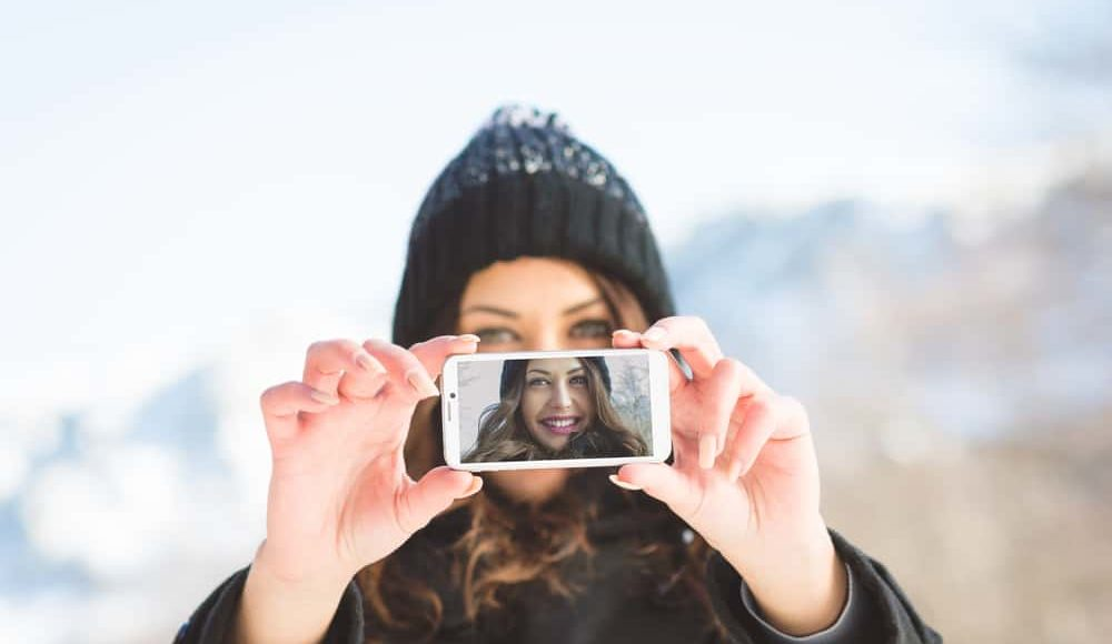 girls with camera taking a selfie. How do know if your social media marketing in Anchorage is effective